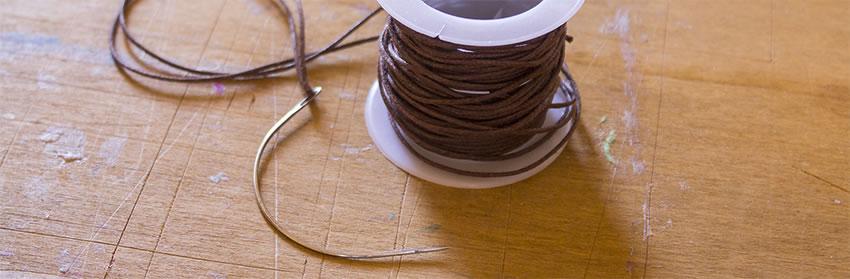 rocchetto di filo cerato con ago per rilegatura